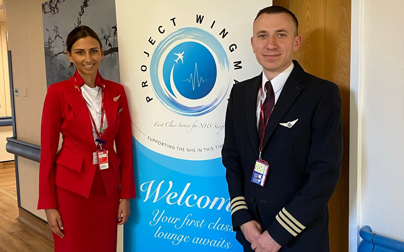 Virgin Atlantic crew stand beside an upright Project Wingman welcome poster