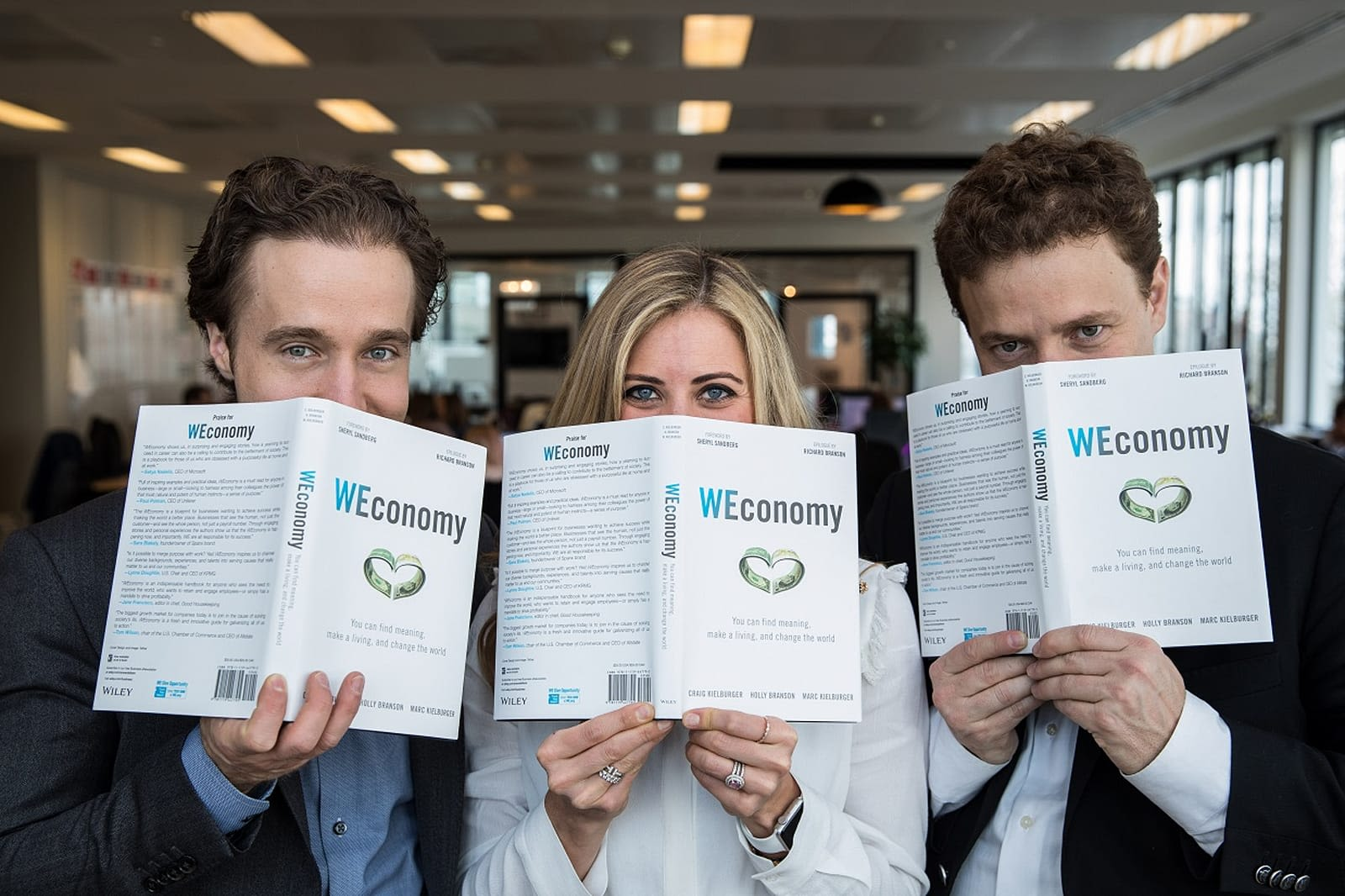 Holly Branson smiles with Marc Kielbrger and Craig Kielberger behind their book copies of Weconomy