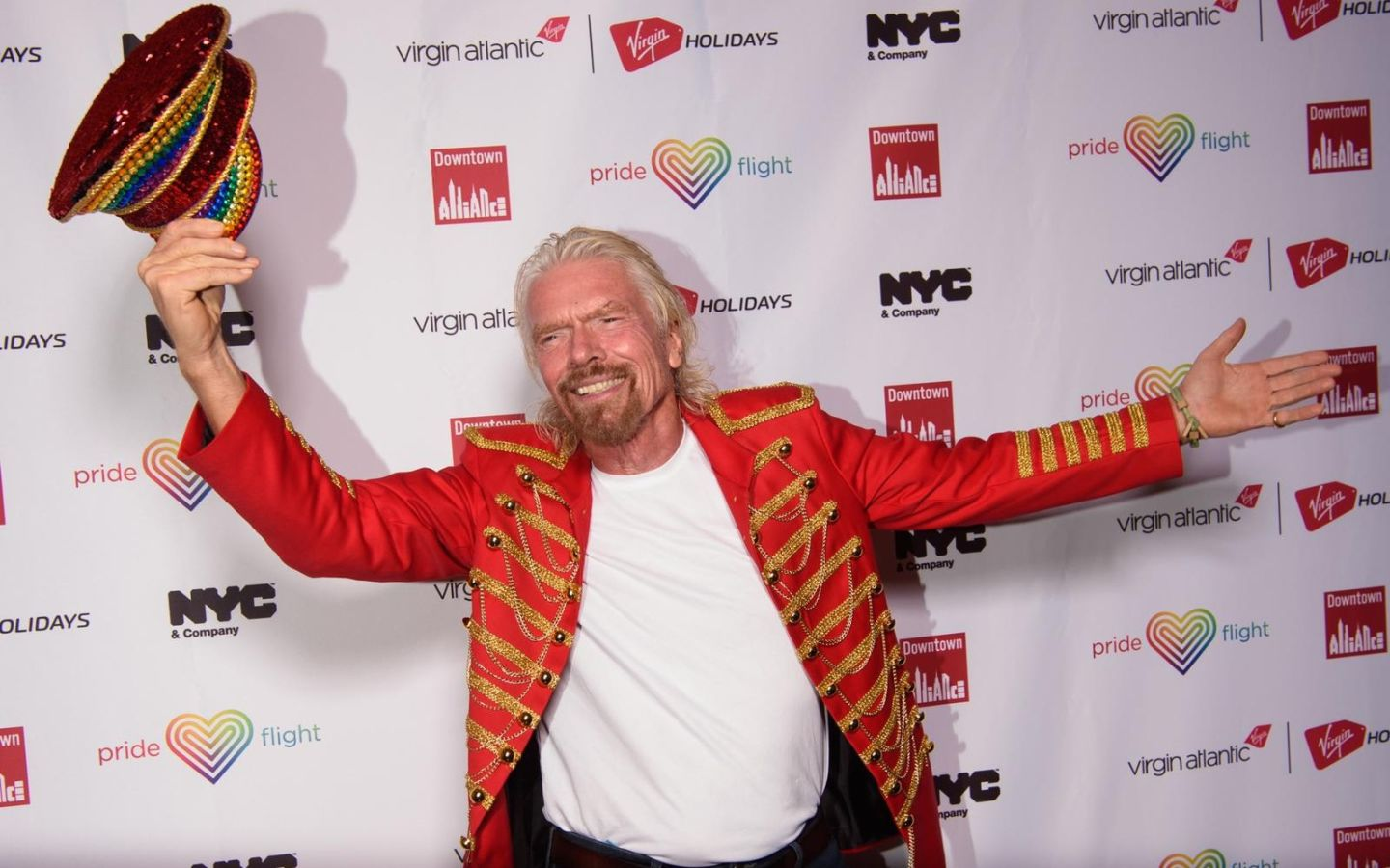 Richard Branson smiling, waving his hat and arms in the air at a Virgin Atlantic Pride event in New York