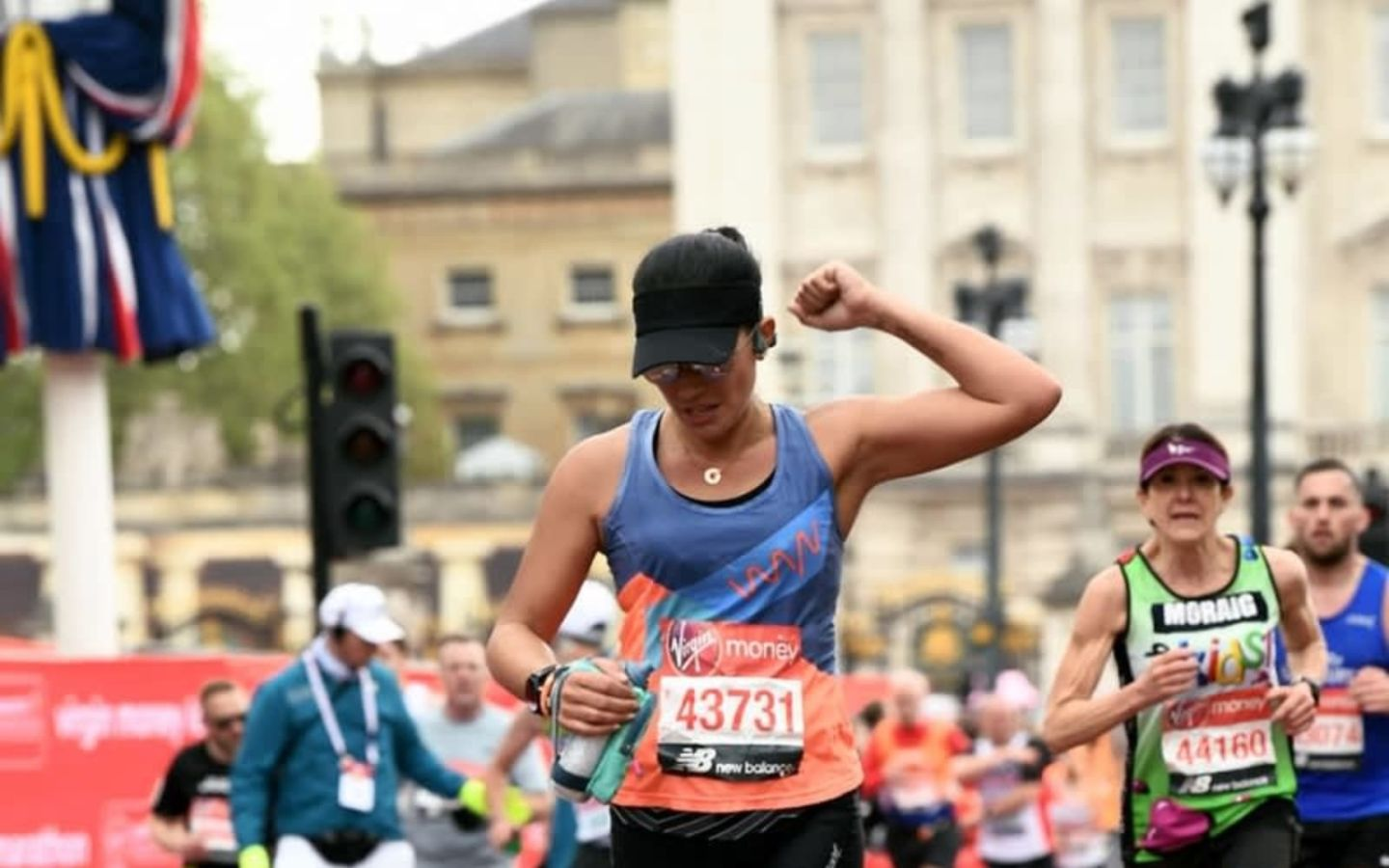 Runner, Lisa Kurdziel wearing black baseball cap raising fist in the air with runners behind her