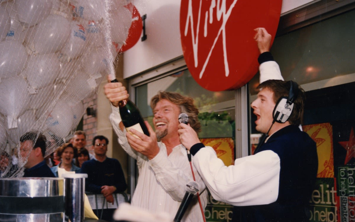 Richard Branson popping a bottle of champagne with a DJ with cheering crowds in the background