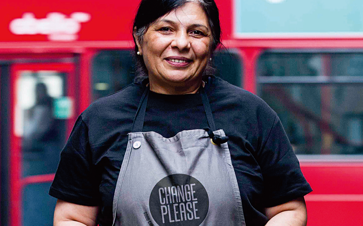 Lady wearing an apron that says change please and standing in front of a red London Bus