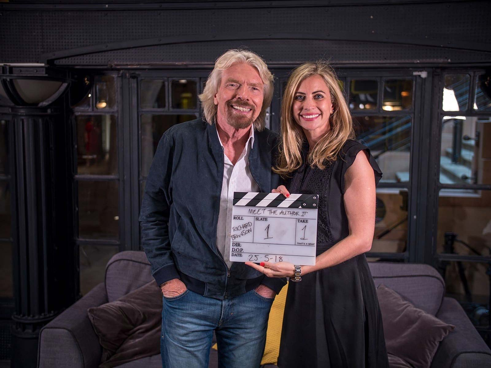 Richard and Holly Branson standing smiling at the camera, Holly is holding a clapperboard