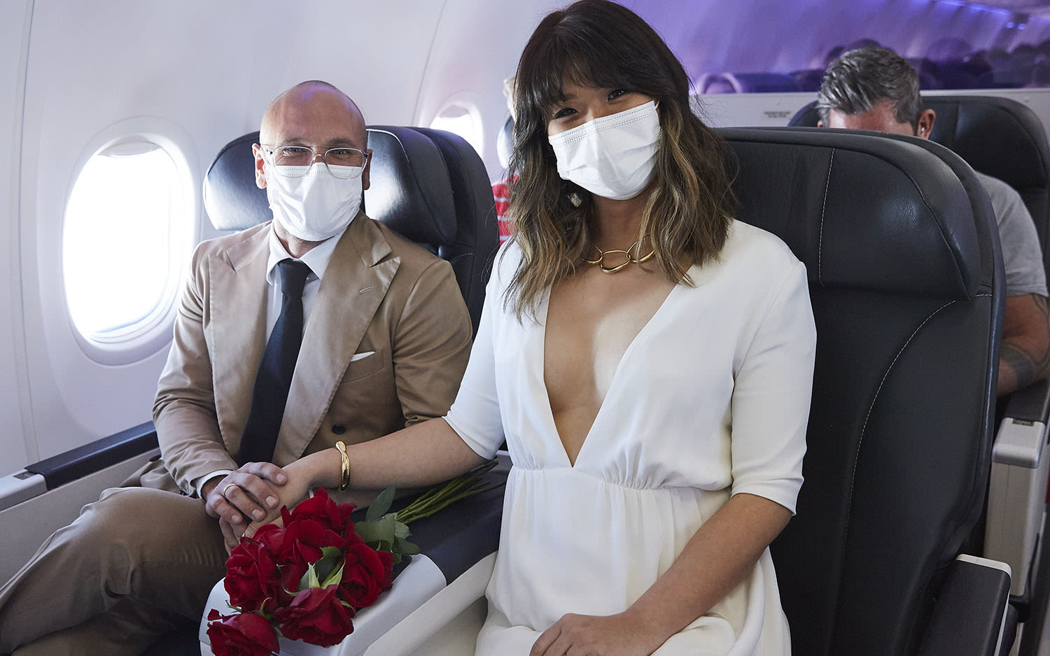 Luke and Elaine Serdar hold hands as they sit on the aircraft after their onboard wedding