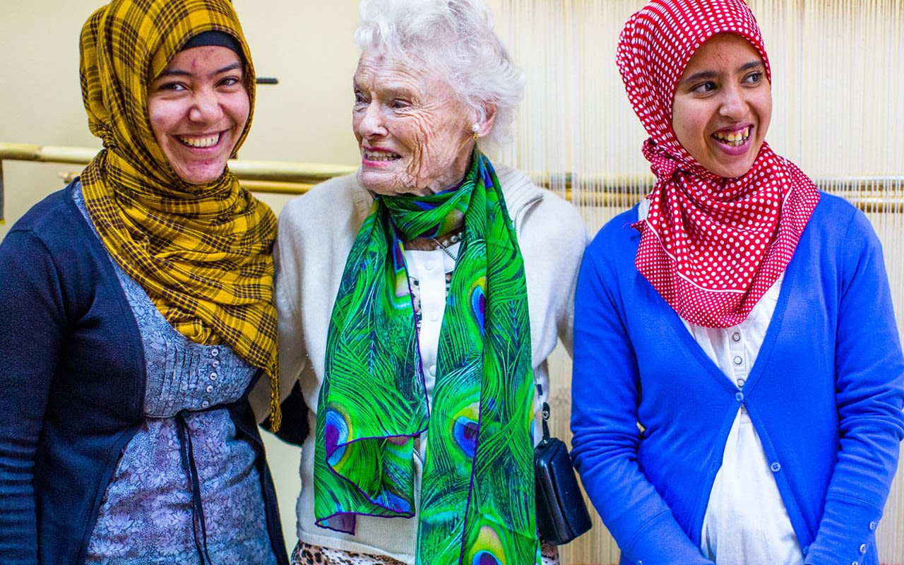 Eve Branson wearing a green scarf in between two ladies with red and yellow headscarves