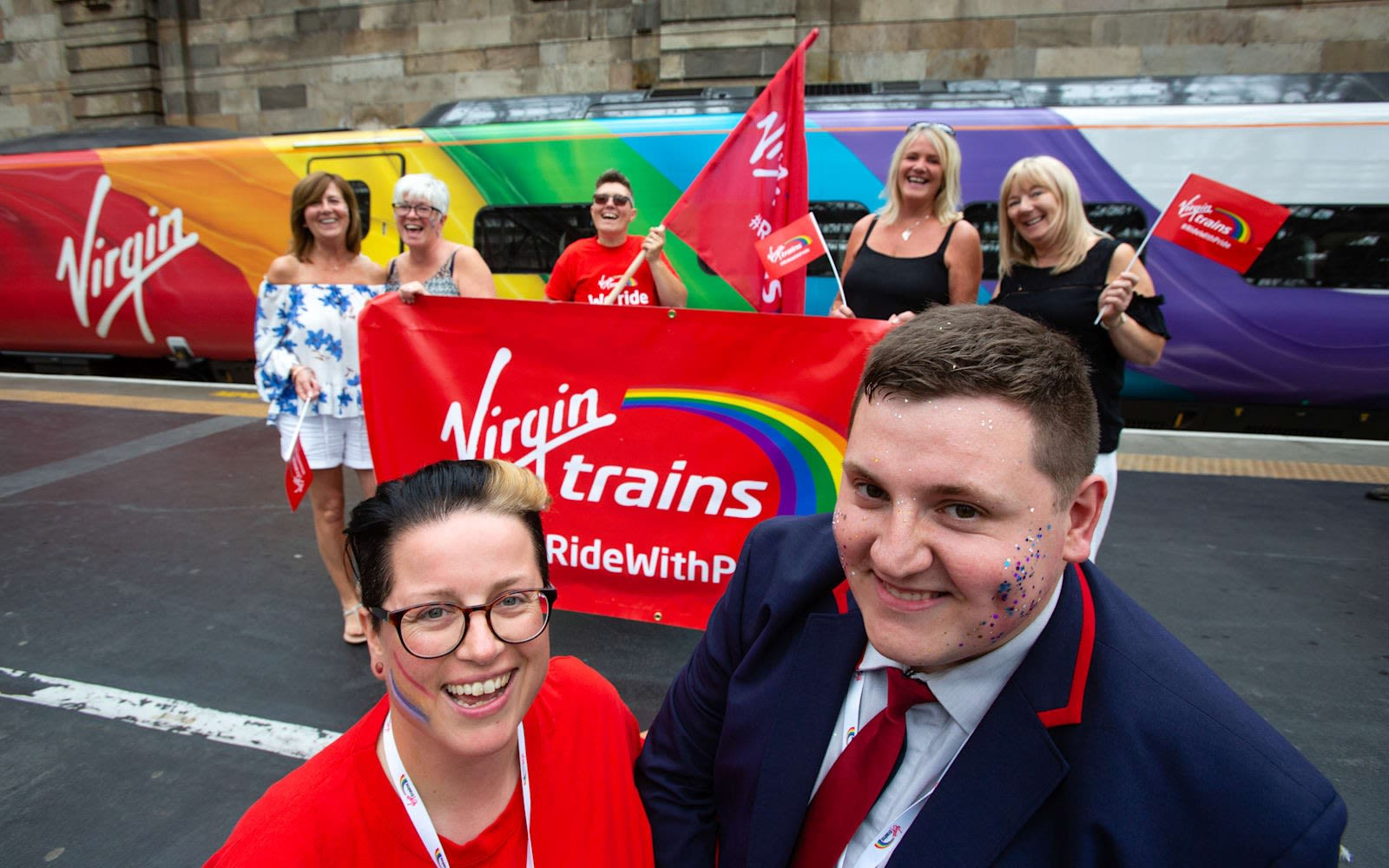 Vic Whitehouse and other Virgin Trains team members celebrate Pride in front of the Virgin Trains Pride train