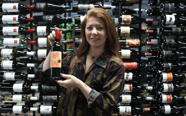 Women holds up a bottle of wine in a wine cellar