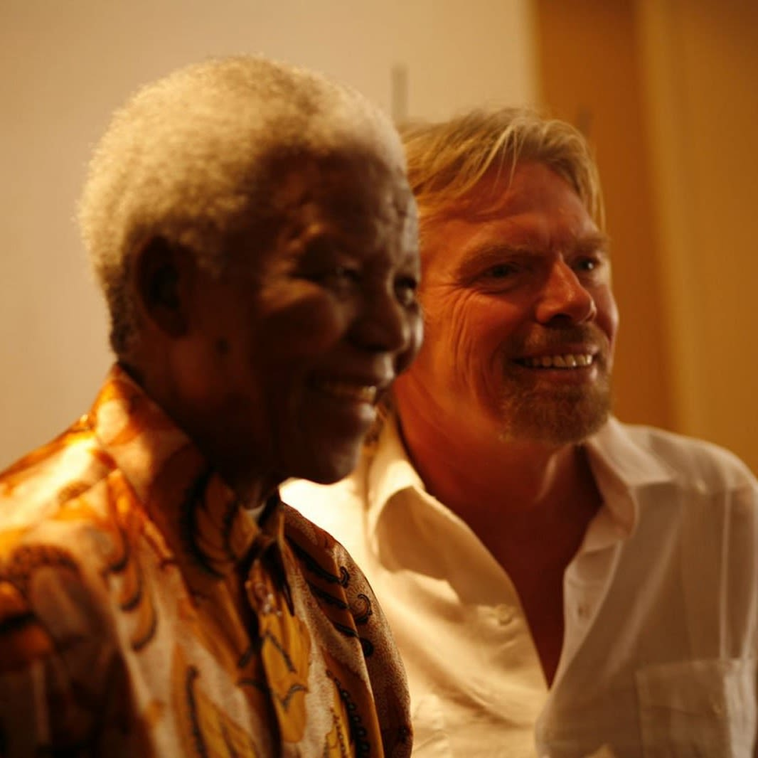 Richard Branson and Nelson Mandela stand together smiling