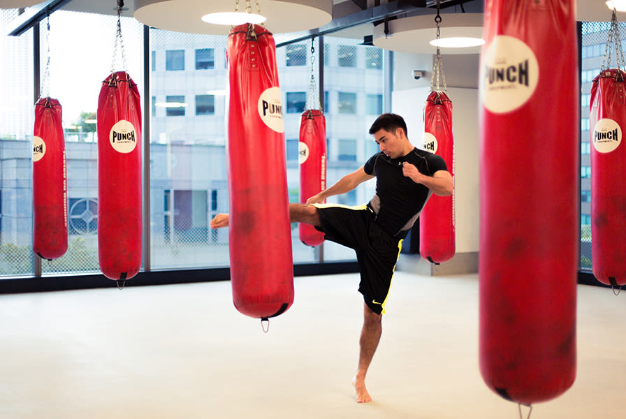 A man kick boxing in an exercise studio at Virgin Active Singapore