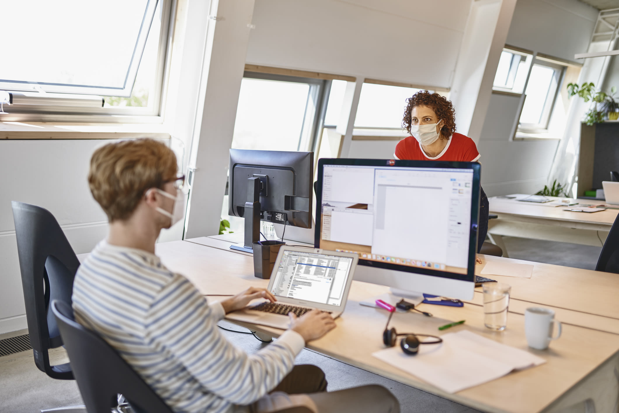 Two colleagues having a discussion across a desk, both wear face masks