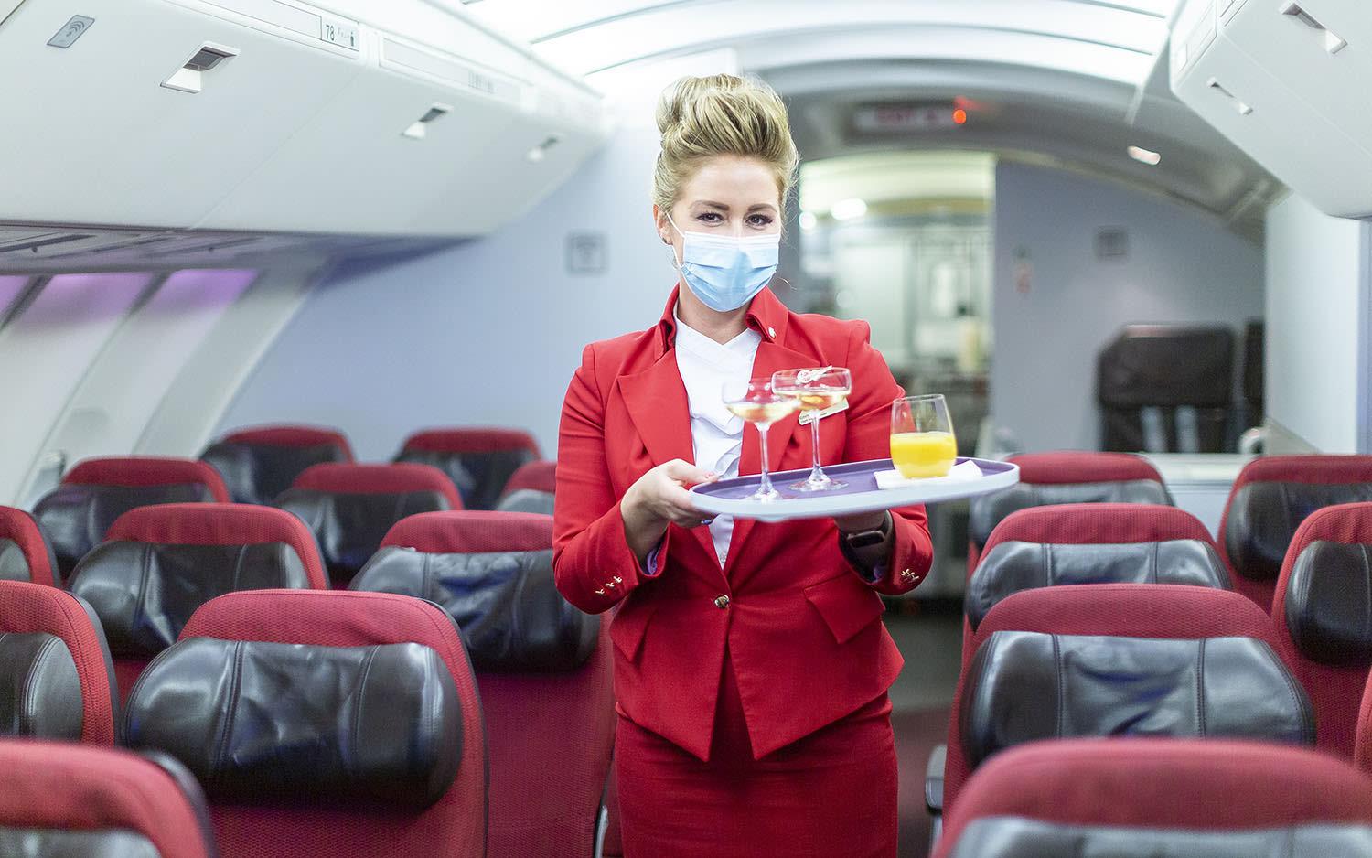 A member of cabin crew stands in the aisle on a Boeing 747 holding a tray of drinks
