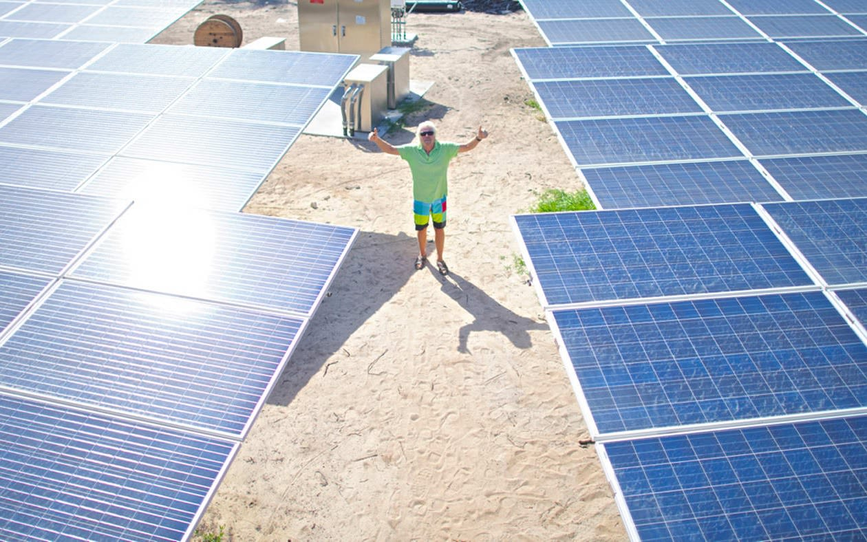Richard Branson with his hands up with large solar panels on each side