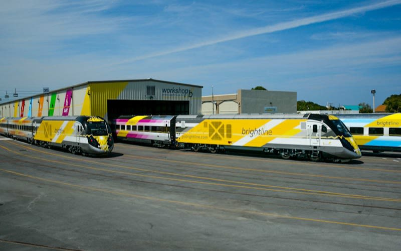 Three Brightline trains with brightly coloured stripes on them