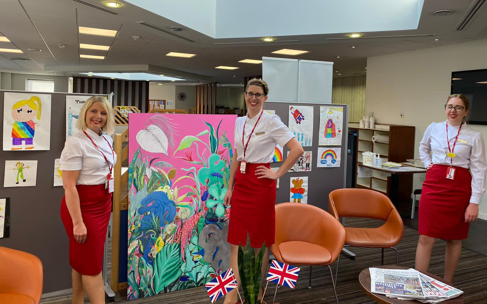 Three crew member pose with some artwork created for the NHS by children. Rainbows and hearts