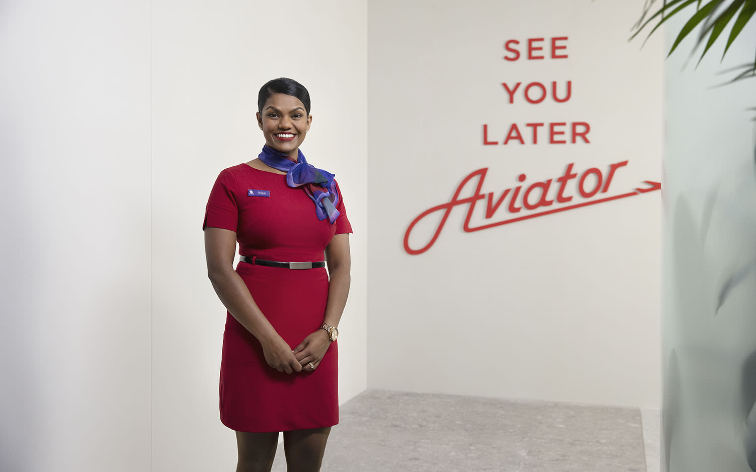 "A member of Virgin Australia cabin crew poses in front of a sign that reads ""See you later aviator"""