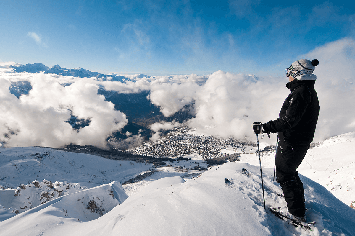 A skier stands on the edge of a slope, looking at the mountains and clouds below