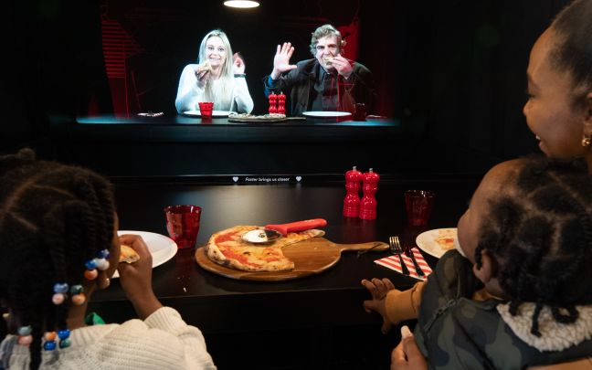 A woman and two young children have dinner with friends via a hologram