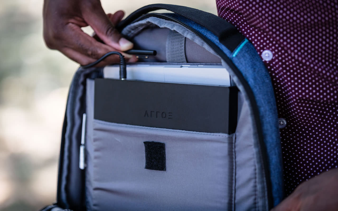 A man plugs in his laptop in a bag that also carries a LAER by Arroe charing device