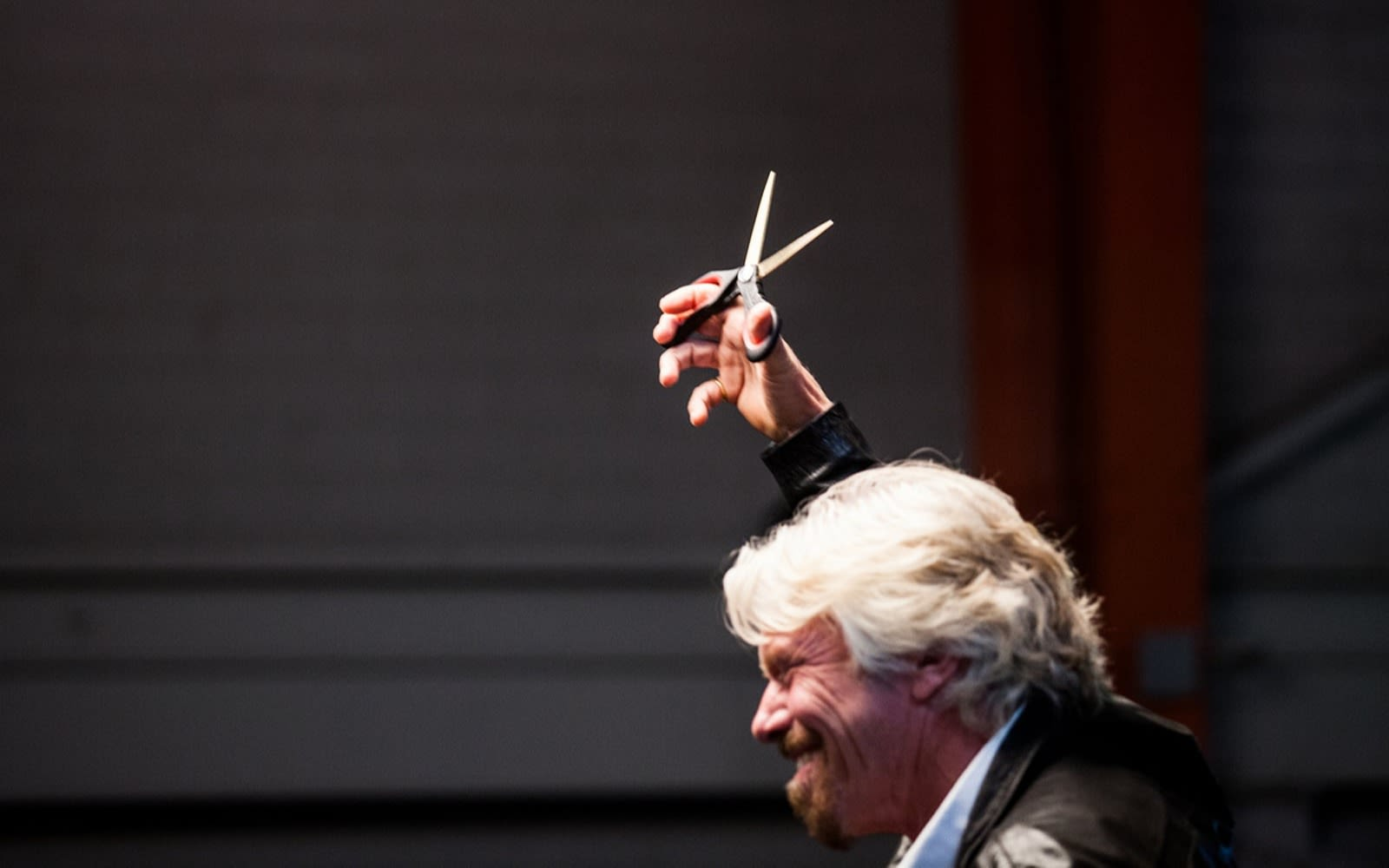 Richard Branson smiling and holding scissors in the air