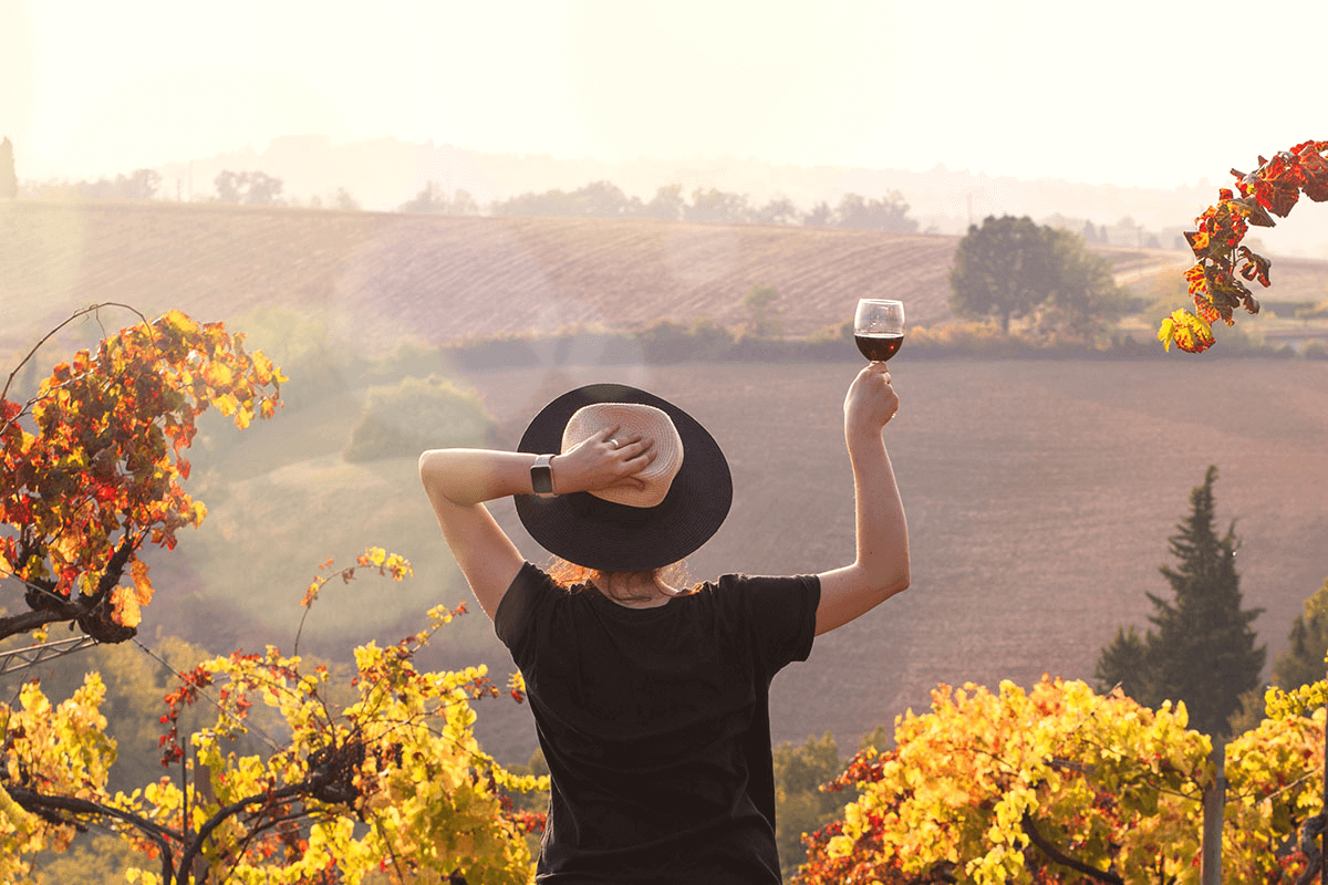 Woman in a hat holds up a glass of red wine and looks out over a winery