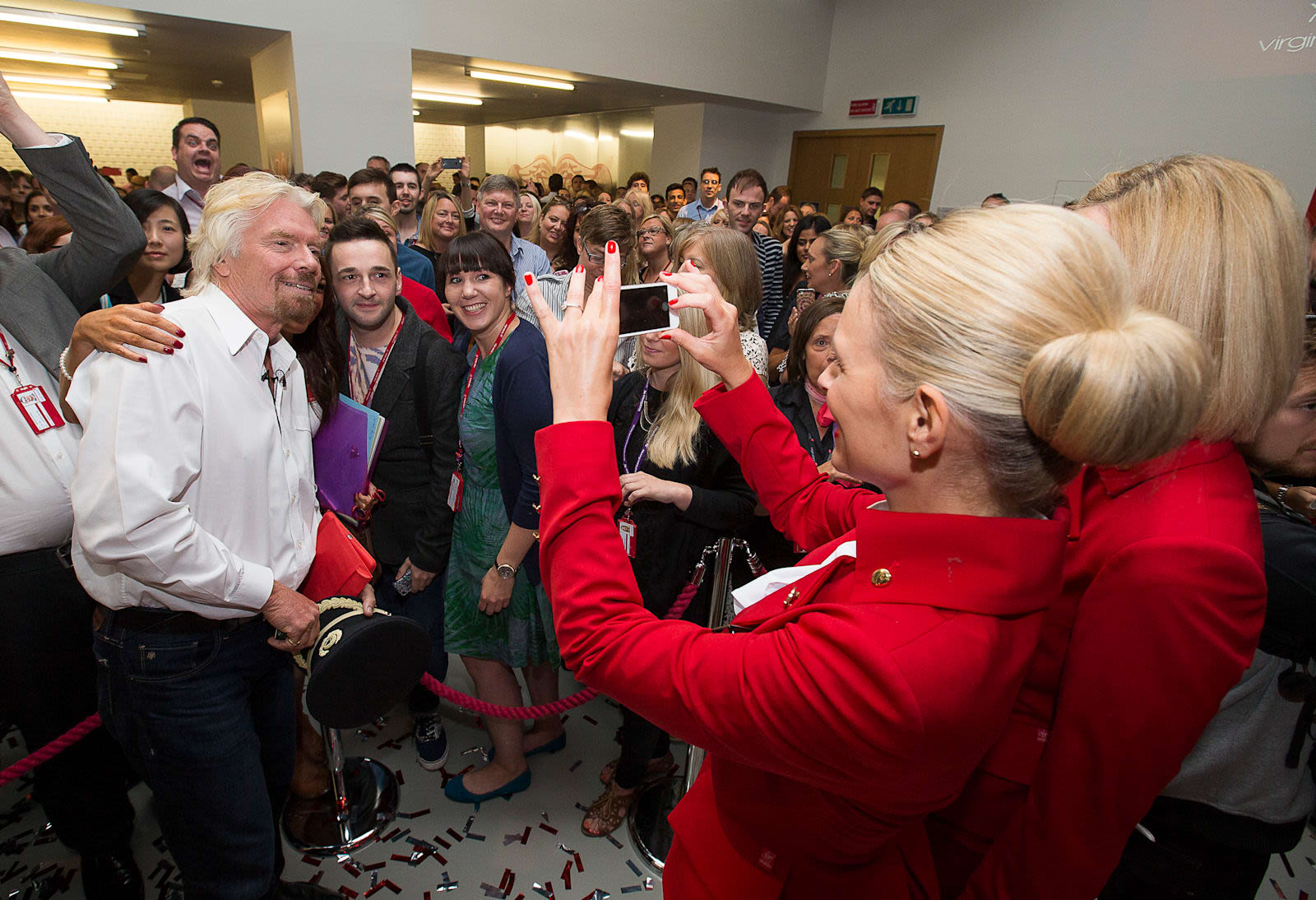 Virgin Atlantic employee taking a picture of Richard Branson and a supporter