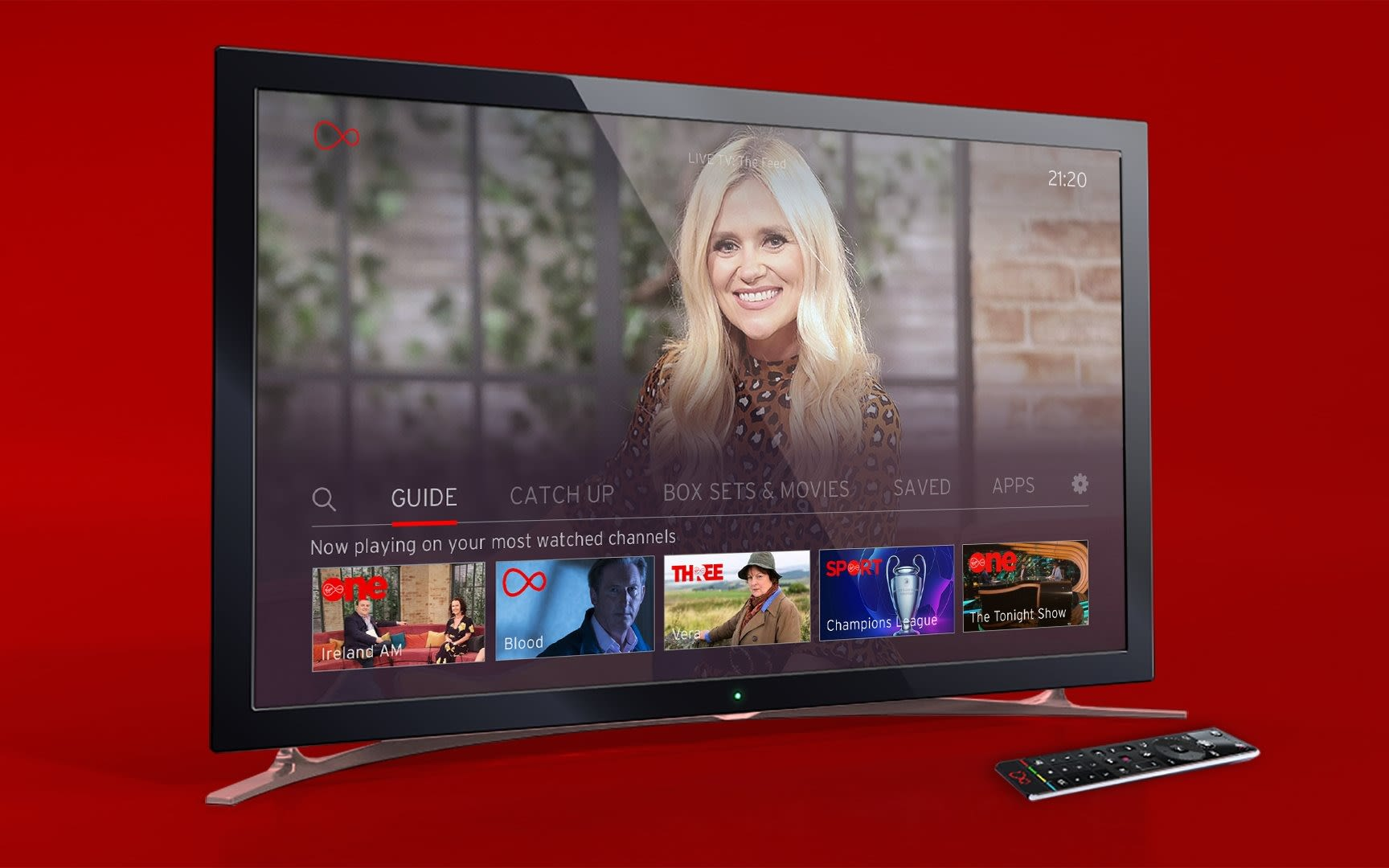 A television with a remote control next to it on a red background