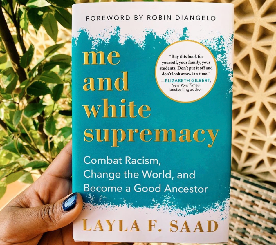 A hand holds the book Me and White Supremacy