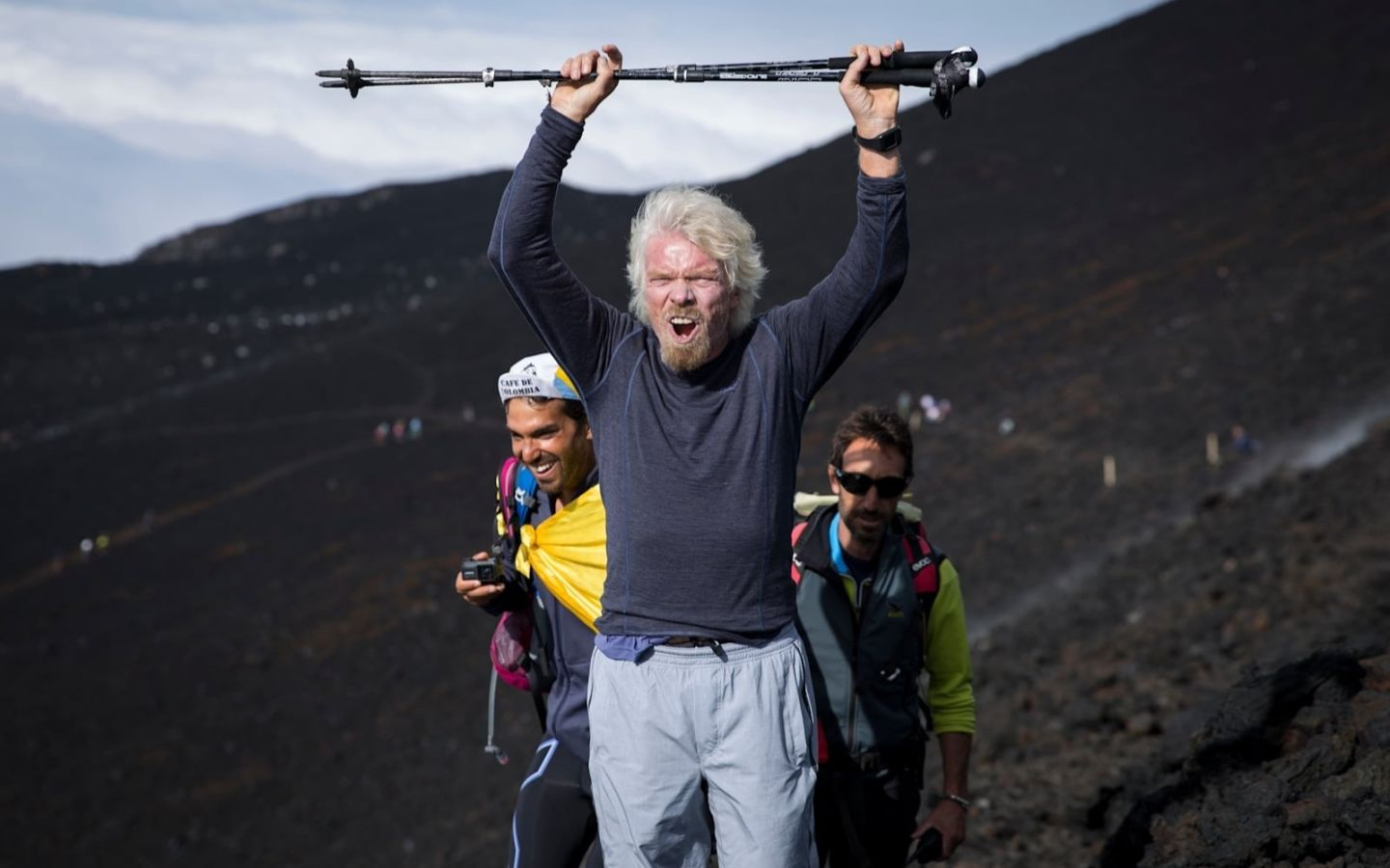 Richard Branson celebrating getting to the top of a mountain