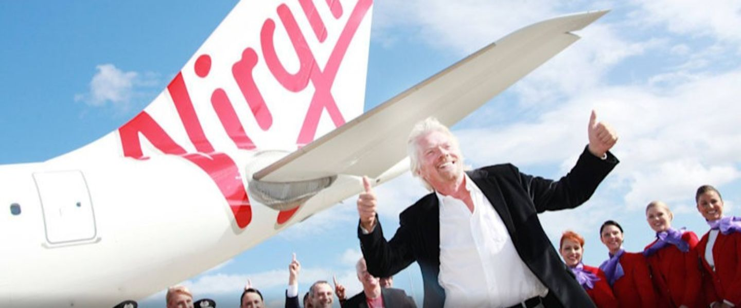 Richard Branson stands smiling with thumbs up, with a Virgin Aircraft and its crew