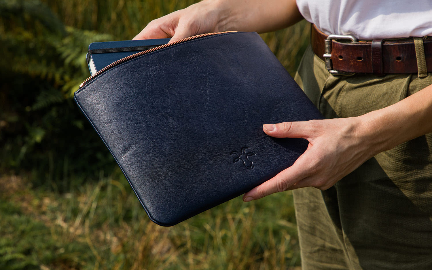 A man holding a leather laptop sleeve