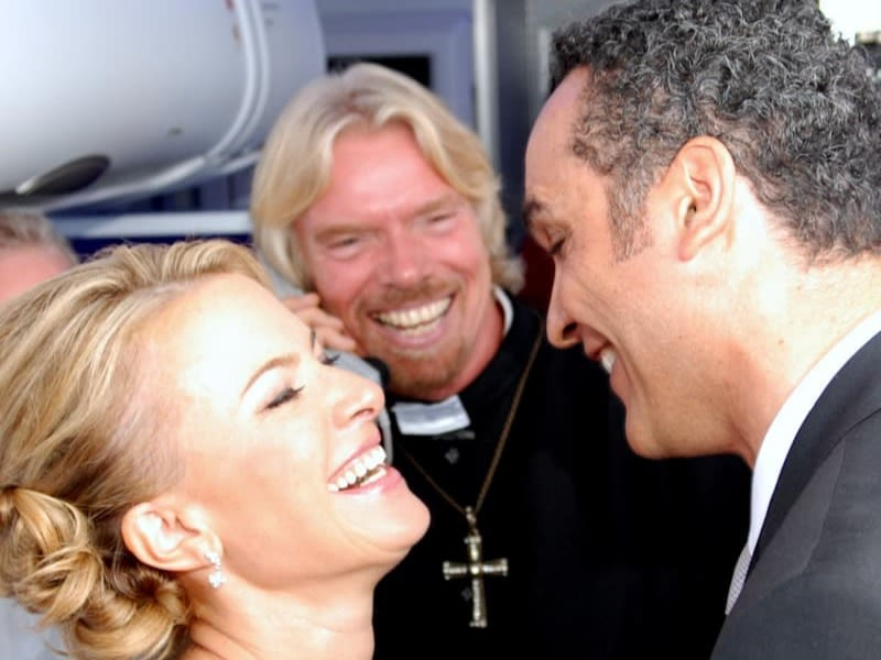 Richard Branson smiling at a newly married couple dressed as a vicar