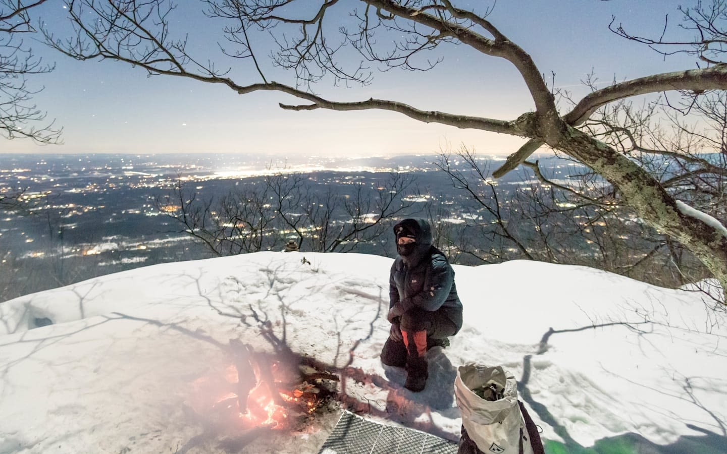 Kate Stone sat on a snowy mountain top next to a small fire