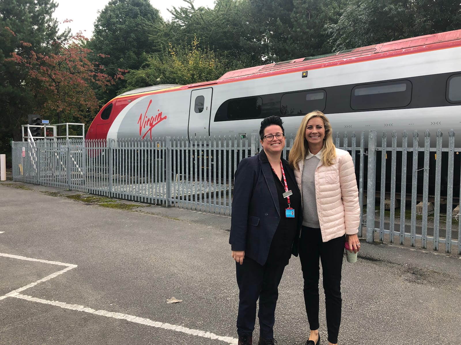 Holly Branson with Vic Whitehouse standing in front of a Virgin Train