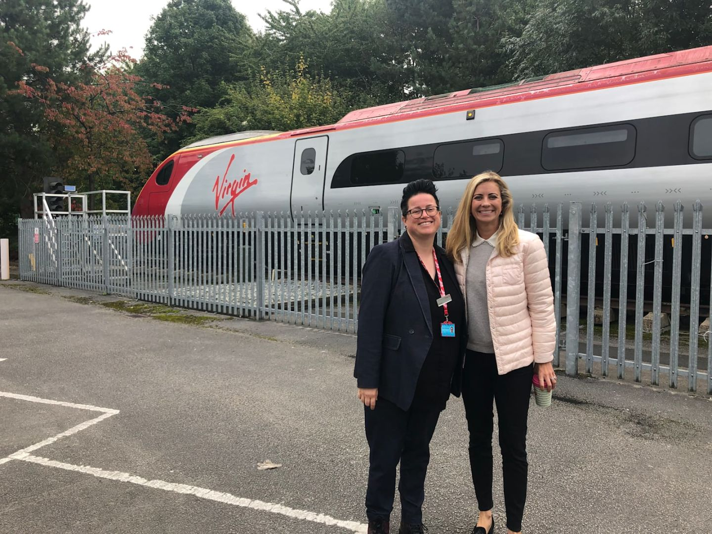 Holly Branson with Vic Whitehouse, smiling at the camera in front of a Virgin Train