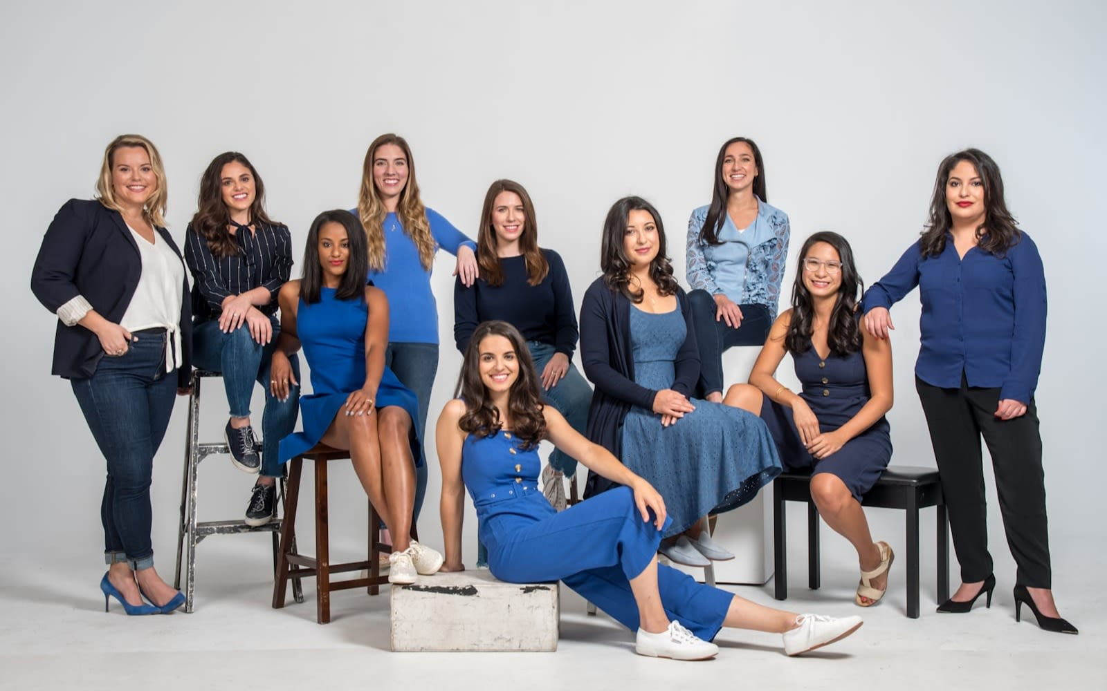 Molly Dillon with nine of her co-authors of Yes She Can smiling for a studio photo