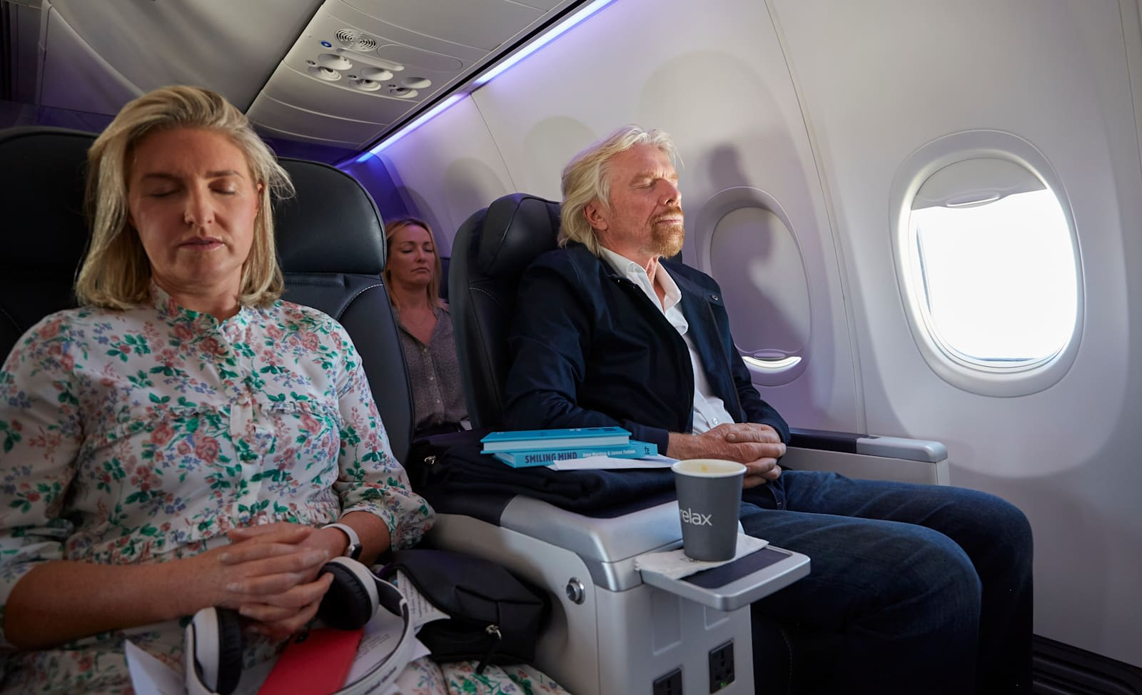 Richard Branson meditates on an aeroplane, with others doing the same around him