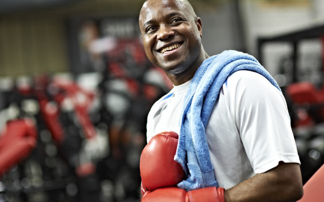 Man smiling in red boxing gloves.