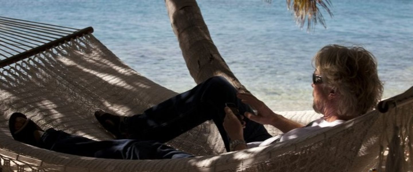 Richard Branson lying in a hammock with the sea in the background