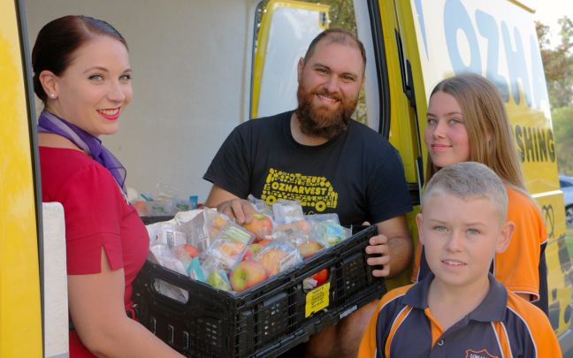A Virgin Australia cabin crew member hands a basket of food to a man and two children outside a yellow van with the OzHarvest logo