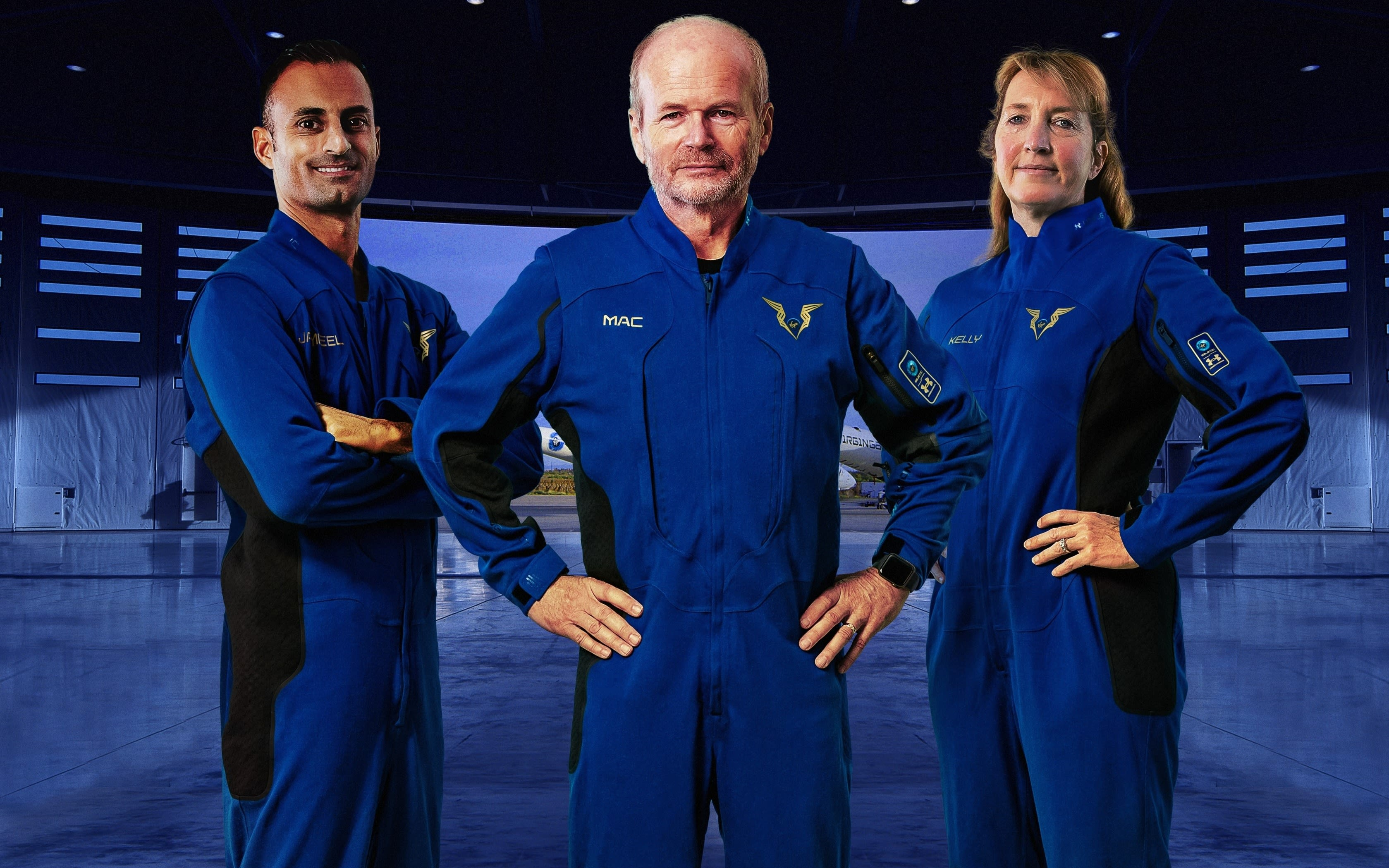 three Virgin Galactic pilots modelling their new spacesuits