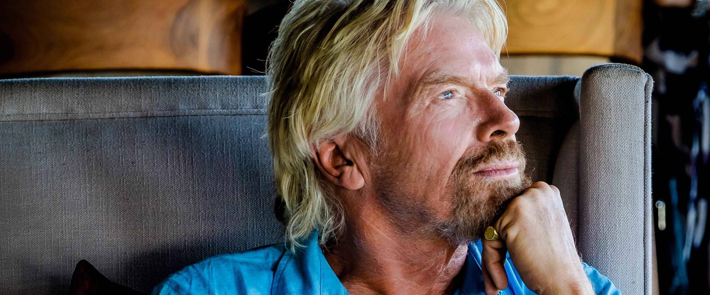 Richard Branson looking to the left with his chin rested on his hand