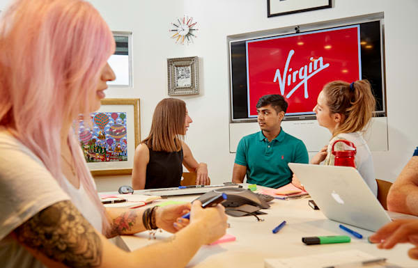 People sitting around a table talking, a screen in the background has the Virgin logo on it
