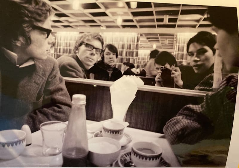 Richard Branson as a young man sits in a restaurant with his friends including Nik Powell