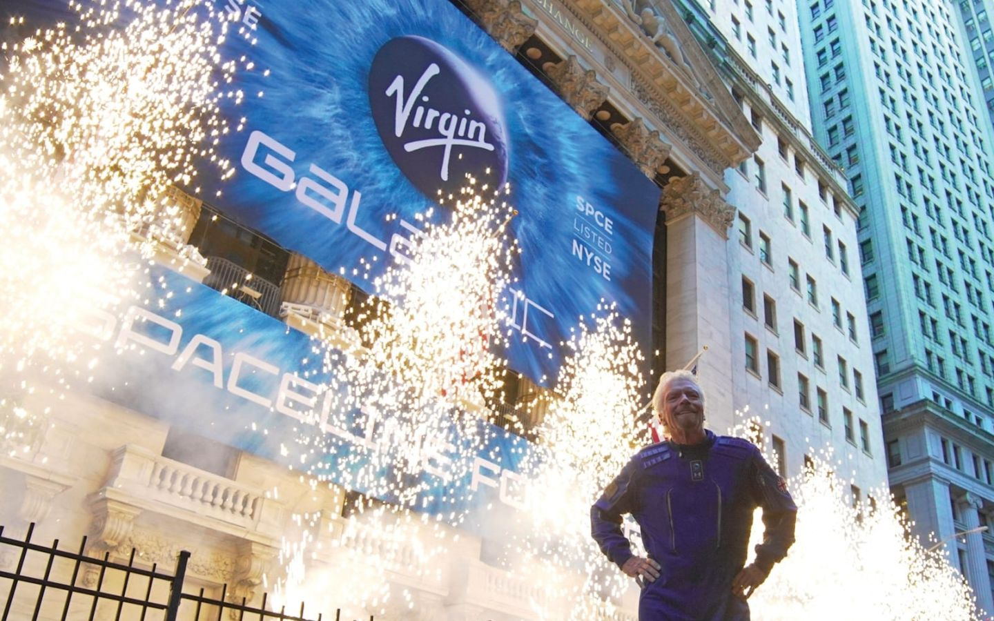 Richard Branson stands in front of pyrotechnics celebrating Virgin Galactic's debut on the New York Stock Exchange