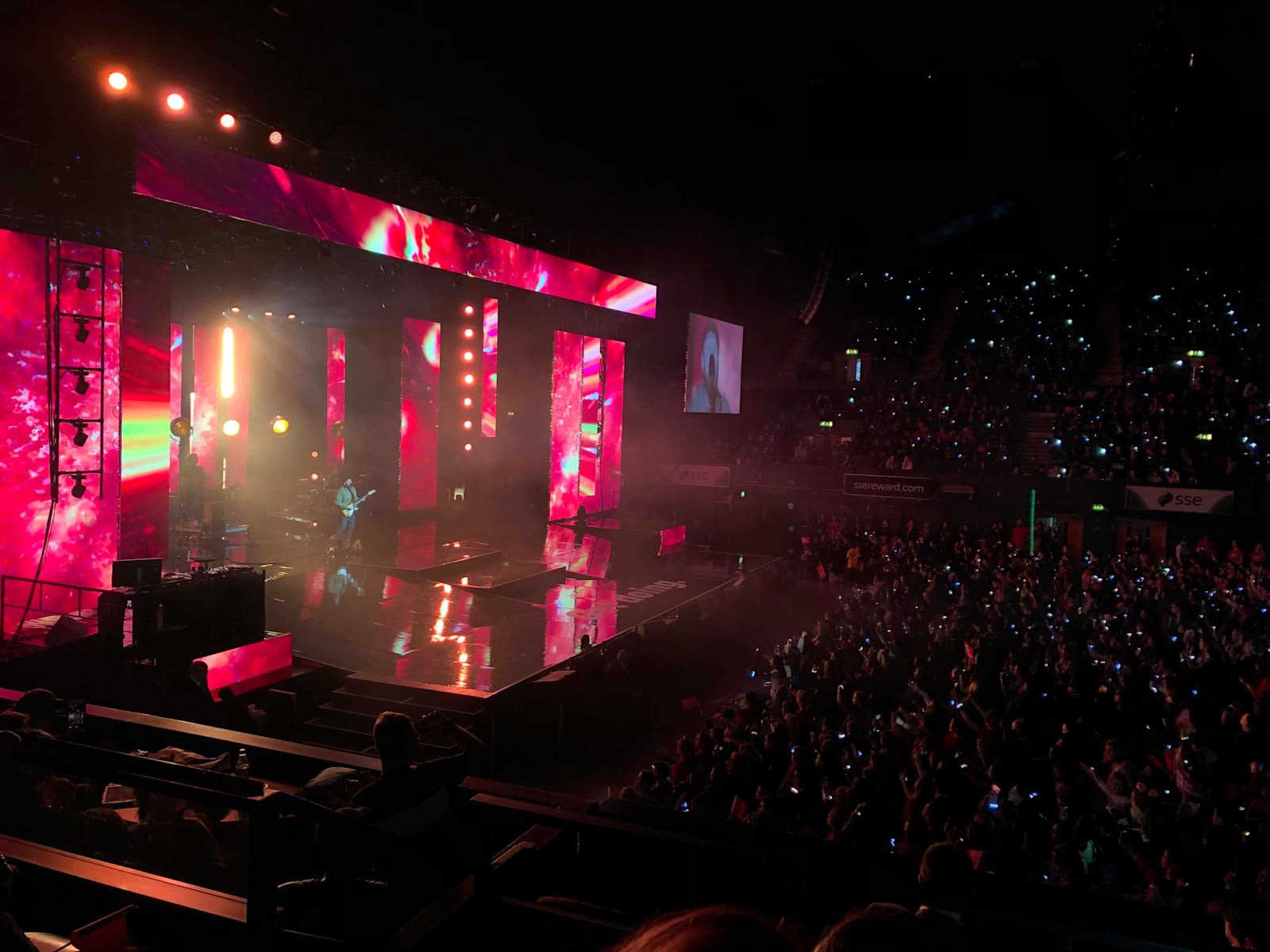 A big stage looking on from the left with pink lighting and a band performing