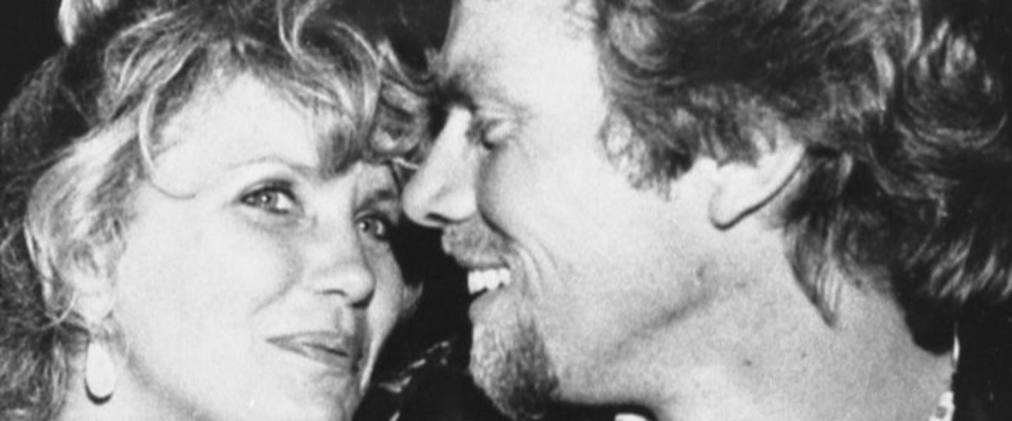 a young Richard Branson and Joan Templeman smile at one another in black and white
