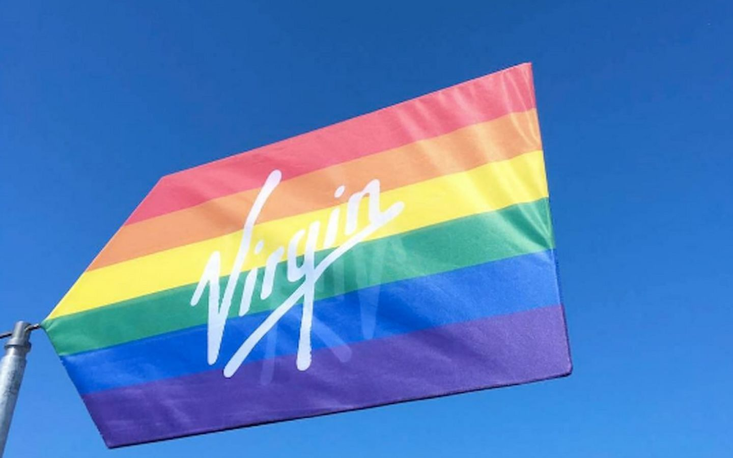 The Pride flag with the Virgin logo across it in white text