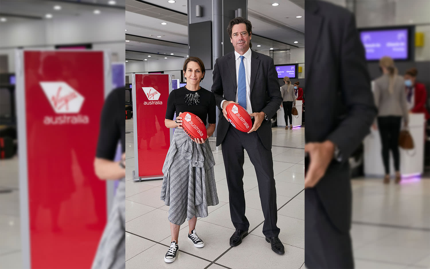 Virgin Australia CEO Jayne Hrdlicka and AFL CEO Gillon McLachlan holding footballs in the departure hall at Melbourne Airport