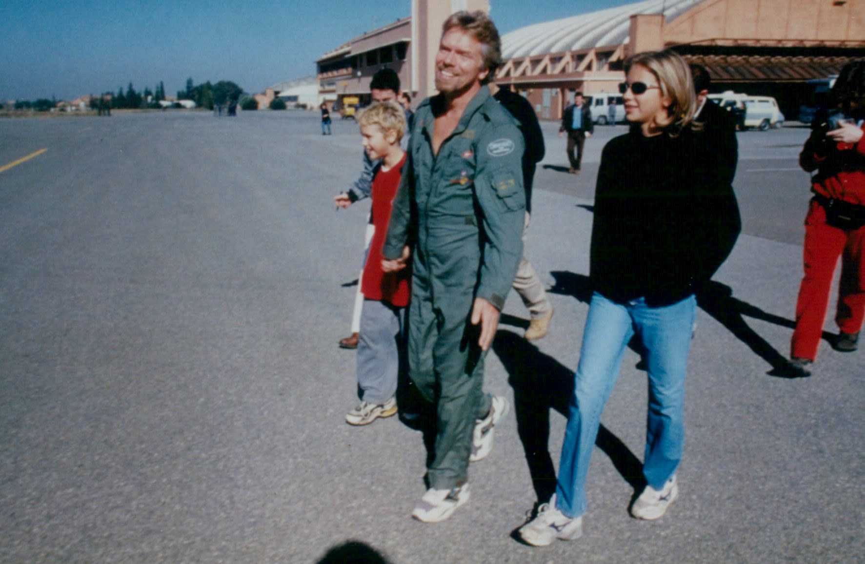 Richard Branson in green jumpsuit with a young Sam and Holly next to him