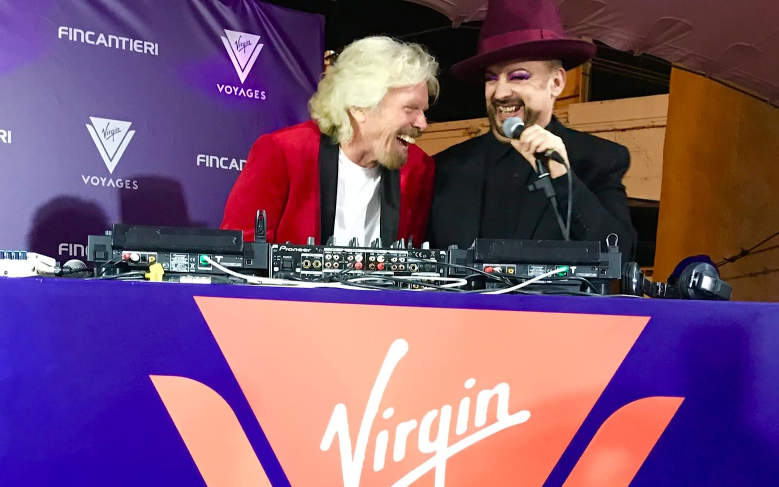 Rihard Branson stands behind decks with Boy George at the Virgin Voyages keel laying party